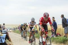 小组骑自行车者乘坐在鹅卵石路的-环法自行车赛 免版税库存图片