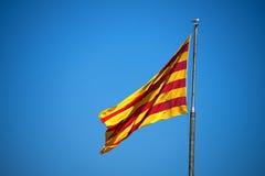 在蓝天的加泰罗尼亚的旗子 免版税库存照片