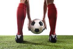 足球运动员的腿红色袜子和黑鞋子的在他的手上的拿着球安置任意球 库存照片