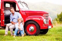 坐在红色葡萄酒汽车的资深夫妇 免版税库存图片
