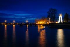 一致点灯塔和一个码头在晚上在格雷斯港, 库存照片