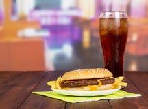 汉堡包用炸薯条,在背景大厅咖啡馆的玻璃可乐 免版税库存图片