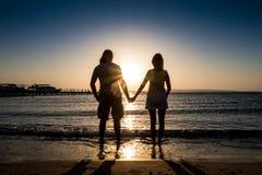 Пары держа руку на восходе солнца захода солнца океана Стоковые Изображения