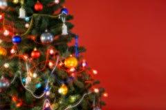 与装饰和光,红色背景的多色圣诞树 免版税图库摄影