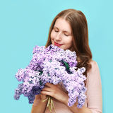 享用花束淡紫色花的气味在蓝色背景的逗人喜爱的妇女 免版税库存照片