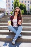 有坐台阶和使用她的智能手机的一个新鲜的杯子的愉快的少妇 免版税库存照片