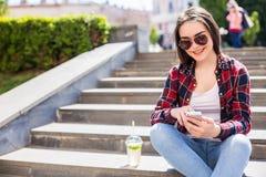 有坐台阶和使用她的智能手机的一个新鲜的杯子的妇女 图库摄影