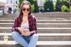 有坐台阶和使用她的智能手机的一个新鲜的杯子的妇女为通信 免版税库存图片