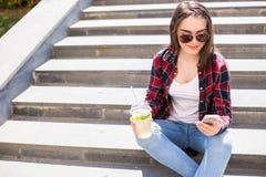 有坐台阶和使用她的智能手机的一个新鲜的杯子的妇女为通信 库存照片