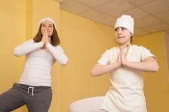 做瑜伽的妇女和青少年的女孩在健身房行使 免版税库存照片