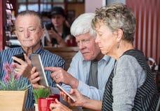 Οι φίλοι στον καφέ στεγάζουν τη χρησιμοποίηση των ηλεκτρονικών συσκευών Στοκ Εικόνες