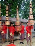 供以人员拿着在宗教队伍的红色和金黄有排列的伞 免版税库存图片