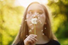Φυσώντας πικραλίδα κοριτσιών εφήβων στη κάμερα Στοκ Φωτογραφίες