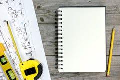 Αρχιτεκτονικό πρόγραμμα με τα εργαλεία και το σημειωματάριο για το γκρίζο ξύλινο γραφείο Στοκ φωτογραφίες με δικαίωμα ελεύθερης χρήσης