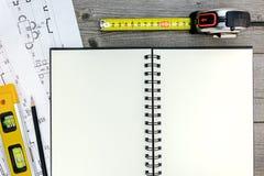 Χώρος εργασίας αρχιτεκτόνων με το σχεδιάγραμμα, τα εργαλεία, το σημειωματάριο και το μολύβι επάνω Στοκ Εικόνες