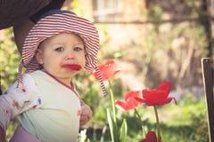 巴拿马草帽的滑稽的女婴走在开花中的公园的在与拷贝空间的晴朗的夏日开花 免版税库存照片