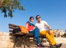 放松在长凳的两个朋友在漫步以后 库存图片