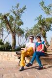 放松在长凳的两个朋友在漫步以后 免版税图库摄影