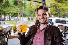 欢呼,敬酒用啤酒和看对照相机的英俊的年轻人微笑,当坐对酒吧柜台时 免版税库存照片