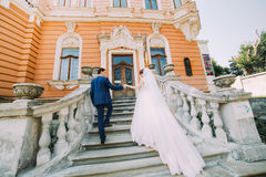 走在浪漫古色古香的宫殿台阶的美好的年轻婚礼夫妇  免版税库存照片