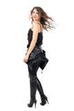 摇滚乐对照相机的妇女轮侧视图与冻结的头发运动 免版税图库摄影