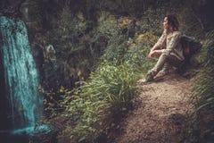 坐在瀑布附近的妇女远足者在深森林里 免版税库存照片