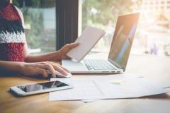 工作在便携式计算机手上的年轻女商人拿着笔记本和巧妙的电话在木书桌上,当坐在咖啡店时 免版税库存照片