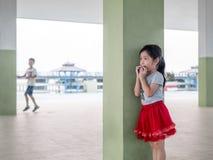 玩捉迷藏的逗人喜爱的女孩 免版税图库摄影