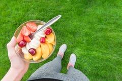 吃水果沙拉的女孩在锻炼以后 免版税库存图片