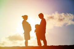 愉快的怀孕的母亲和父亲有儿子的日落的 免版税库存图片