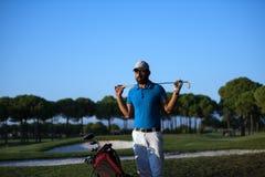 在高尔夫球场的高尔夫球运动员画象日落的 库存照片