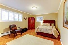 有绒面革褐色床的舒适大客房和装甲、硬木地板和米黄墙壁 图库摄影