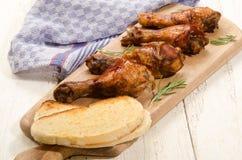 用烤肉汁用了卤汁泡在木板的小鸡腿 免版税库存图片