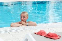一个游泳池的一个白肤金发的少妇与红色比基尼泳装由水池离开 库存照片