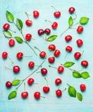俏丽的样式由与绿色的甜樱桃制成在浅兰的破旧的别致的背景离开 免版税库存照片