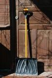 有橙色把柄的黑塑料雪铁锹在木门 免版税库存照片