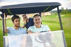 在他们的高尔夫车的可爱的家庭 库存图片