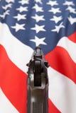 与手枪的被翻动的旗子在它系列-美利坚合众国 库存图片