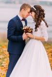 年轻在湖岸秋天桔子的新婚佳偶新娘夫妇的肉欲的片刻充分离开 免版税库存照片