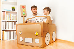 生和他的驾驶手工制造纸板汽车的儿子 库存照片