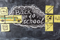 回到白垩写的学校的标题在被画的黑黑板和校车在纸 免版税库存照片