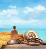 晒黑化妆水和凉鞋在海滩 免版税库存照片