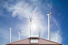 热水系统的太阳电池板在的屋顶和蓝色的风轮机 库存照片
