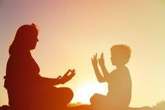 Силуэт матери и сына делая йогу на пляже Стоковое Изображение