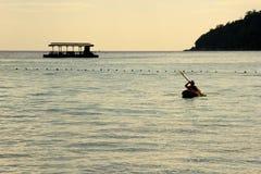 在皮船的人划船在日落 免版税图库摄影