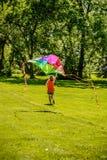 妇女赛跑和飞行的五颜六色的风筝 免版税库存照片