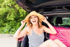 假期,旅行概念-少妇准备好旅途带着手提箱的暑假和汽车 库存照片