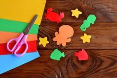 纸海洋动物-章鱼,鱼,海星,海象,螃蟹 色纸板料,在木背景的剪刀 免版税库存照片