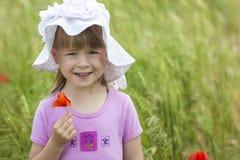 举行红色花和微笑的帽子的小逗人喜爱的女孩 免版税库存图片