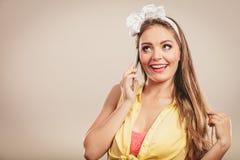 女孩的减速火箭的别针谈话在手机 免版税库存图片